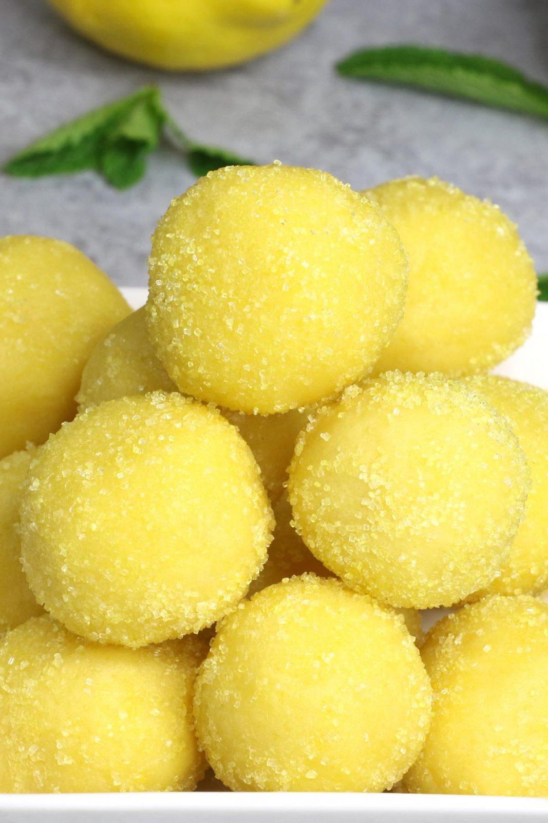 Homemade lemon truffles on a white plate.